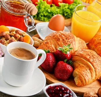 Breakfast consisting of croissants, coffee, fruits, orange juice, coffee and jam. Balanced diet.